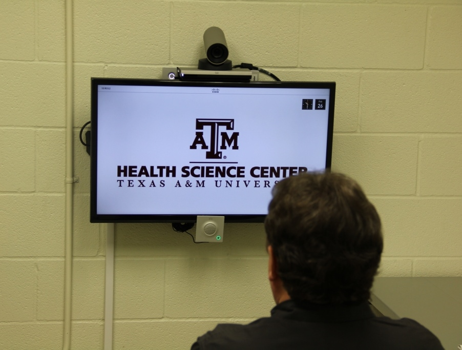 Man looking at TV monitor with Texas A & M logo on it